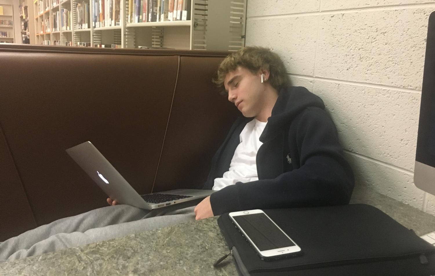 Friends Select Student sleeps in class while trying to finish work.