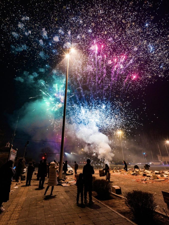 The bell rang at zero o'clock, and people on the street picked up their phones to take pictures of the bright fireworks. The father and son in the center of the photo just finished setting off their own box of fireworks.